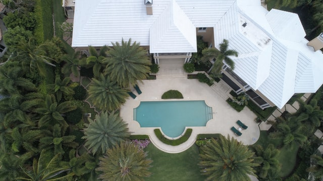 An aerial view of a house with white roof and beautiful swimming pool